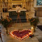 ein Herz aus Rosenblättern und Lichtern und eine Kerze für Karla