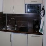Eine kleine Einbauküche mit Kühlschrank, Geschirrspülmaschine und Backofen.