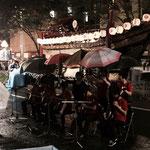雨の中、仲間さす傘の下での演奏は、和胤初