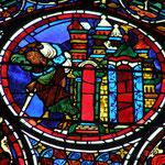 En haut du vitrail commence le récit de la parabole. Un homme lourdement chargé de ballots de marchandises et appuyé sur un bâton franchit la porte d'une ville (Jérusalem).