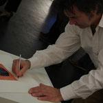 Alexander Arundell Grafiker, bei der Signierung einer Grafik