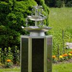 Edelstahlbrunnen -  Gartenbrunnen aus Edelstahl mit Efeuranken auf Granitsäule (© Raven Metall Design)