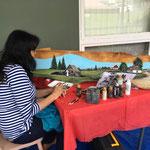 Julie Champagne peint sur un banc de bois (symposium 2017)