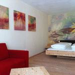 """Vitalhotel Rainer, Val d'Ultimo, Alto Adige - pittura su parete e stampe su tela """"stanza dell'Arnica"""""""