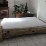 Bett aus halbiertem Birnbaumstämmen