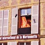 石造りの家の窓で、シュールな人形劇が・・・。