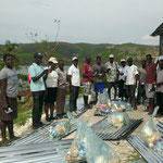 Les producteurs de la coopérative COPVECA avec leur kit (tôles, denrées alimentaires et produits d'hygiène)