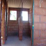 10. Juni 2015: Im Erdgeschoss sind alle Zimmer gemauert - der Installateur arbeitet schon und setzt die Leitungen.