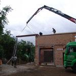 13. Juli: Die Steher sind einbetoniert, und der erste Dachbalken wird aufgelegt.