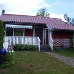 Ferienhaus, Vorderseite mit Terasse und Garten