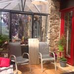 Véranda vitrée, un mur de pierres où se trouvent des chaises de repos, des plantes du gite de la gorre en location en ardeche