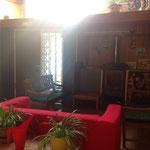 le coin repos, un canapé rouge devant le poele de bois du gite de la gorre en location