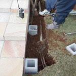 フェンスの基礎となるコンクリート製スタンドブロックを柱位置に合わせて埋め込みます