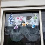 音符ステッカーとピアノサインステッカーを窓に貼り付け