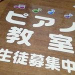 透明ビニールクロスに文字を貼り、内側からガラスにテープで貼付け