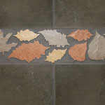 Autumn-colored porcelain leaves with a brown porcelain field tile. Strong and durable enough for floors or walls, inside or outside.