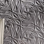 Intricate swirls built into gray triangular tiles.