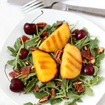 Grilled peach and arugula salad with bacon, cherries, and pecans