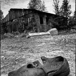 Im Vordergrund alter kaputter Schuh, Hintergrund altes baufälliges Gebäude.