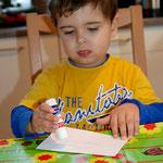 Tim streicht Klebe auf ein weißes Blatt Papier...