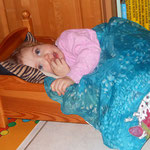Schon seit langem legt sich Nelly in das Puppenbett. Sie muss sich schon sehr klein machen, um noch hinein zu passen.