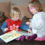 Nelly und Fiona schauen zusammen ein Buch an.