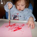Nach dem Handabdruck malt Nelly auch noch mit dem Pinsel.