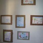 Die einzelnen Kunstwerke an der Wand im Gruppenzimmer der Kindergruppe