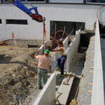 Betonwinkelelemente werden als Abtreppung in die Böschung versetzt