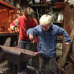 Kajetan und Stephan teilen sich den Amboß. Sie schmieden Hammerkeile und üben dabei viele Grundtechniken der Metallumformung.