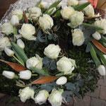 Weiße Rosen und Tulpen im Steckschwamm arrangiert. Schleifen können bestellt werden
