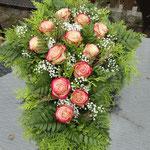 Trauerflorisitk: Kreuzrohling, mit frischen Rosen gesteckt
