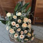 Trauergesteck mit Rinde und aprikotfarbenen Rosen