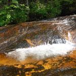⑤八幡平・黒谷地、八幡平の山頂付近の残雪が徐々に融けて、温泉水の影響を受けた赤い河床を磨き、北上川に注ぎます。