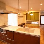ペニンシュラタイプのキッチンからリビングを望む ヤマハのキッチンは人口大理石のクオリティ高し
