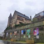 Im Hof rund um das Schloss heitert eine farbenfrohe Kunstausstellung die triste Regen-Atmosphäre auf