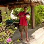 """dieser """"Künstler"""" hält mit einer Hand die Kokosnuss und schlägt sie mit der anderen auf"""