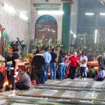 Während die Einheimischen ehrfürchtig beten schauen sich die Touristen die Kirche an