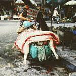 Für Supermarktbesucher ein verstörender Anblick - Schweinehälften werden mit dem Moped durch die Hanoier Altstadt transportiert.