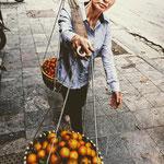 Eine mobile Händlerin unterwegs in der Hanoier Altstadt. Auf ihren Schultern lasten ca. 30 kg.