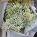 Een katoenen tas vol met vlierbloesemtrossen