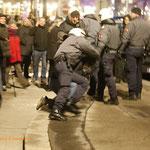Ein Polizist greift sich einen vermeintlichen Demonstranten aus der Menge und prügelt auf ihn ein.