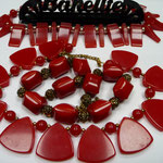 Three red bakelite necklaces. With the little brass roses: €270. With the wedges:€380. Three-cornered pieces: €340