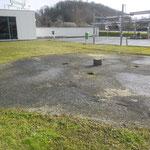 Het schachtdeksel bevindt zich tussen een tankstation en een carwash.