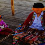 Eine Frau eines bestimmten Volksstammes webt eine Decke mit tradiotionellem Muster