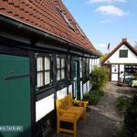 Links Seitenansicht des Ferienhauses mit Klönschnackbank im Innenhof. Das Häuschen am Bildende sieht zwar wohnlich aus, ersetzt aber nur raren Kellerraum.
