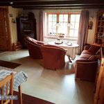 Wohnzimmer: Bei Sonnenschein kaum genutzt, bei widrigem Wetter sollte der Kachelofen links in Aktion treten (ja klar, Zentralheizung gibt es außerdem). Vorne links im Bild der Esstischbereich.