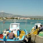 Vissers zijn hun netten aan het repareren in het haventje van Ireon.