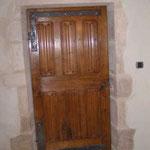 Porte intérieure de style gothique réalisée en vieux bois de chène. Panneaux en plis de serviette et traverse centrale sculptée de rinceaux.