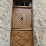 Porte extérieure d'esprit Louis XIII réalisée en bois de chène. Sous-bassement reprenant le style des portes de Bourgogne. Partie supérieure en chevrons embrevés.